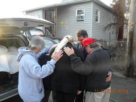 In November 2012 Eddie and ministry partner Carol BlueJacket pray with family in Staten Island, NY who lost their home to Hurricane Sandi